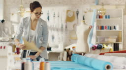 Beautiful Female Fashion Designer Straightens Roll of Blue Fabrics and Lays Out Templates on it.  She Works in a Light Colourful Studio Full of Various Clothes, Fabrics and Sketches on the Wall.