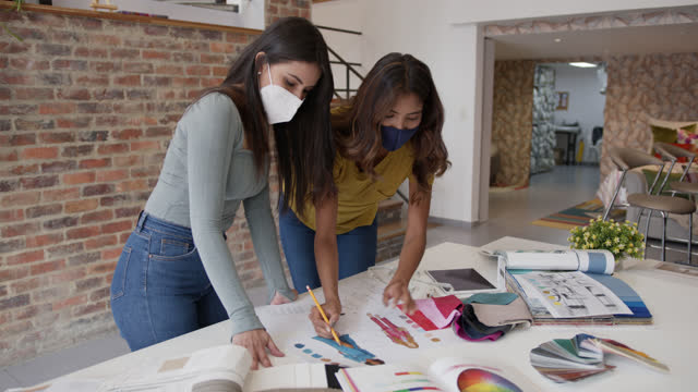 beautiful female fashion designers working on a new collection looking at the sketches and fabric swatches both wearing protective face masks - fashion collection stock videos & royalty-free footage