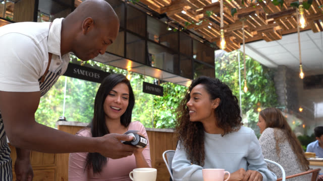beautiful female friends enjoying coffee and paying the bill with credit card to friendly waiter - paying restaurant stock videos & royalty-free footage