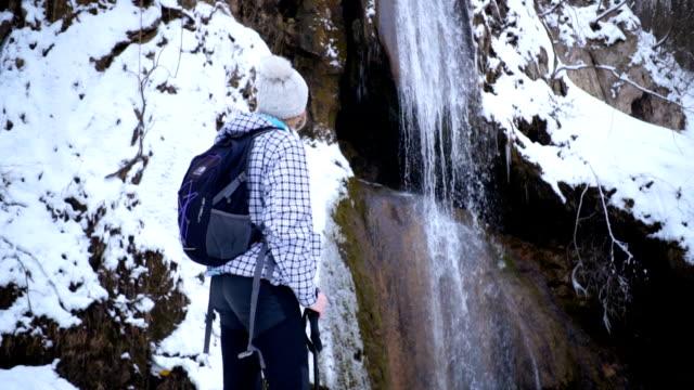 Prachtige vrouwelijke wandelaar kijken naar majestueuze waterval