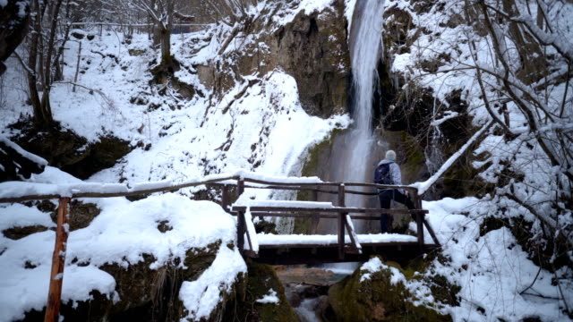 Prachtige vrouwelijke wandelaar wandelen in de buurt van de waterval