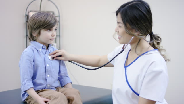 Beautiful female nurse checking young male patients heart rate