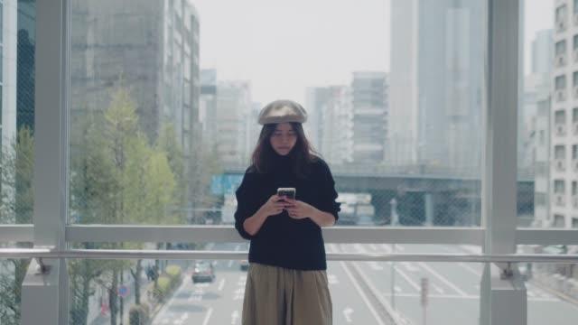stockvideo's en b-roll-footage met mooie vrouwelijke kantoormedewerker maakt gebruik van smartphone zittend op haar werkbureau - internet surfen