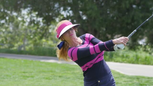 vídeos y material grabado en eventos de stock de hermosa mujer toca profesional jugador de golf - swing de golf