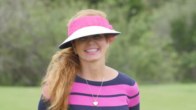beautiful female professional golfer smiles - sun visor stock videos & royalty-free footage