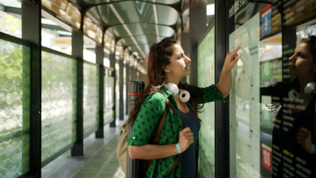 beautiful female student at the bus stop looking at the bus line on map - bus stop stock videos & royalty-free footage