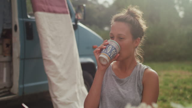 vídeos de stock e filmes b-roll de beautiful female surfer drinking coffee in a field in front of van - acordar