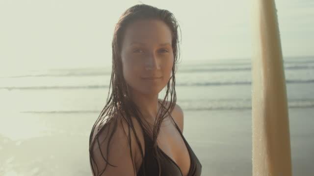 vídeos de stock, filmes e b-roll de beautiful female surfer in bikini holding surfboard, standing on deserted beach in the south of france in summer - biarritz