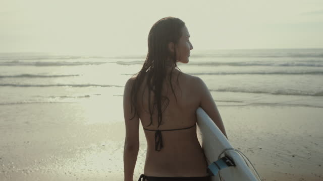 Beautiful female surfer in bikini looking out at sea with surfboard at Atlantic ocean beach in the summer in South of France