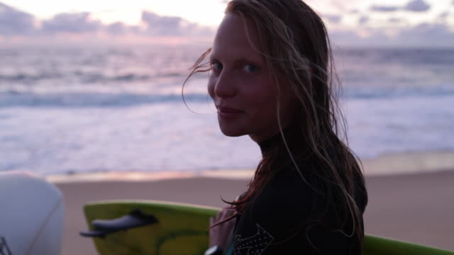 Beautiful female surfer looking into camera at the beach in Southern France