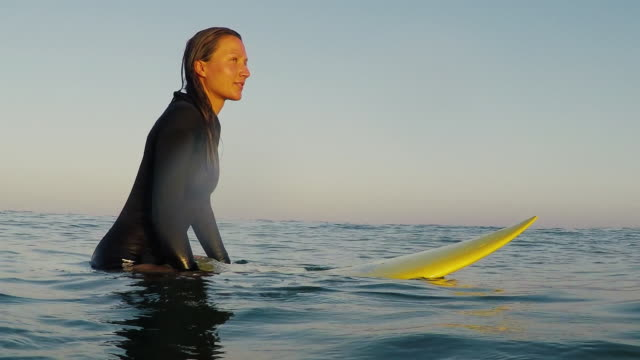 Beautiful female surfer looking out over ocean, sitting on surfboard in sunset at deserted sandy beach at Atlantic ocean coast in the south of France.