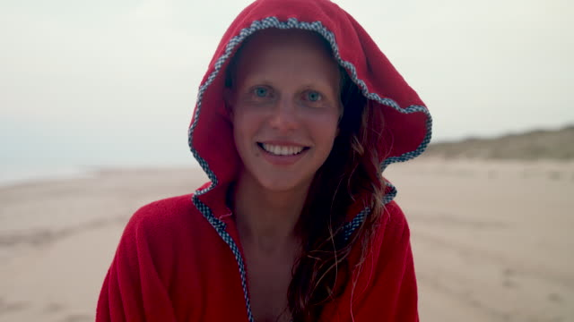 beautiful female surfer putting on red hooded towel/poncho after surf on beach at atlantic ocean coast in south of france. - towel stock videos & royalty-free footage