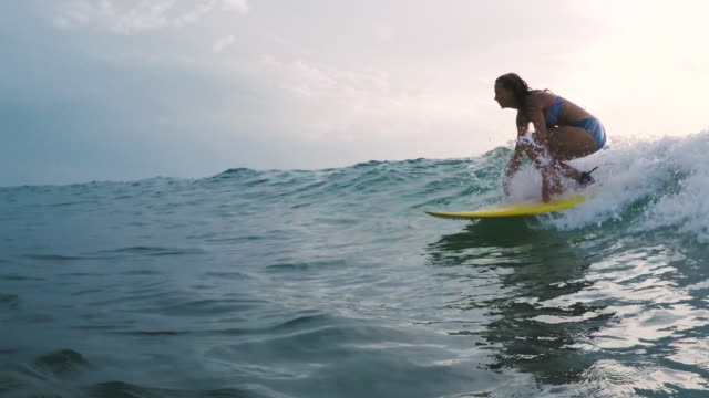stockvideo's en b-roll-footage met beautiful female surfer riding wave in bikini on yellow surfboard at sunset in atlantic ocean in southern france. - surfen