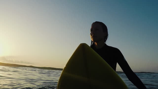 beautiful female surfer sitting on surfboard at sunrise in surf break and waves at deserted sandy beach at atlantic ocean coast in the south of france. - 情熱点の映像素材/bロール