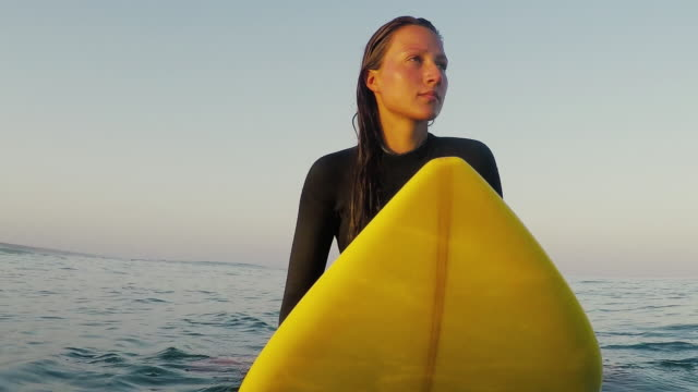 vídeos de stock, filmes e b-roll de beautiful female surfer sitting on surfboard at sunrise in surf break and waves at deserted sandy beach at atlantic ocean coast in the south of france. - biarritz