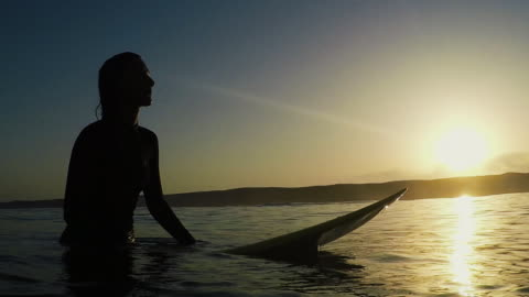 beautiful female surfer sitting on surfboard in sea at sunset at deserted sandy beach at atlantic ocean coast in the south of france. - surfboard stock videos & royalty-free footage