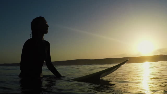 vídeos de stock, filmes e b-roll de beautiful female surfer sitting on surfboard in sea at sunset at deserted sandy beach at atlantic ocean coast in the south of france. - surfe
