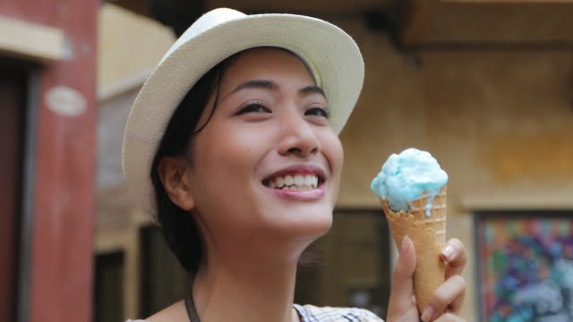 beautiful female tourist wearing a hat and eating ice cream on summer holidays - ice cream stock videos & royalty-free footage