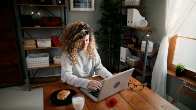 Beautiful female using laptop and having breakfast in the kitchen