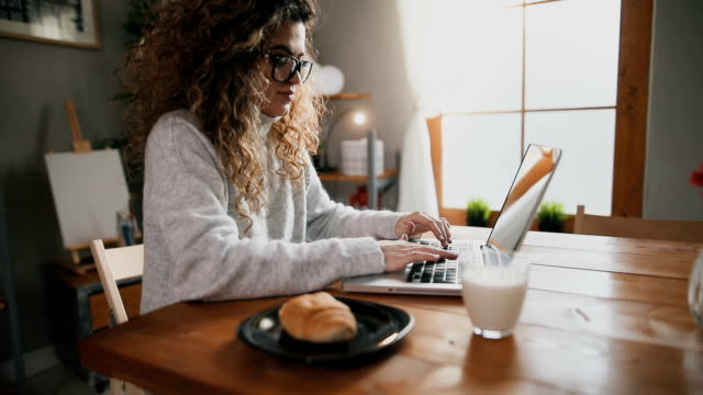 beautiful female using laptop and having breakfast in the kitchen - surfing the net stock videos & royalty-free footage