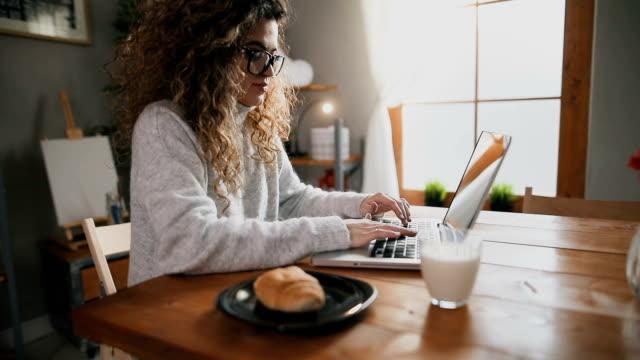 stockvideo's en b-roll-footage met mooie vrouw met laptop en ontbijten in de keuken - internet surfen