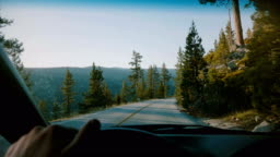 Beautiful first person view of male hand holding car steering wheel driving along mountain road in Yosemite slow motion.
