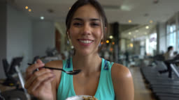 Beautiful fit woman at the gym taking a break eating a parfait while facing camera smiling