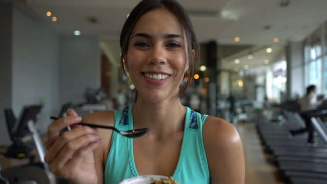 beautiful fit woman at the gym taking a break eating a parfait while facing camera smiling - eating stock videos & royalty-free footage