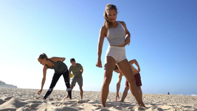 beautiful fit woman leading group of people stretching at the beach - fitness instructor stock videos & royalty-free footage