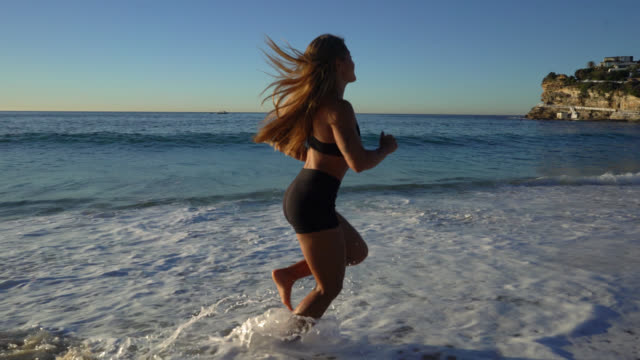 Beautiful fit woman running at the beach barefoot