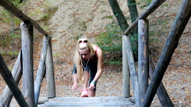vídeos de stock, filmes e b-roll de bela fitness feminino modelo amarrar seu cadarço de sapato antes de correr ao ar livre - laço acessório