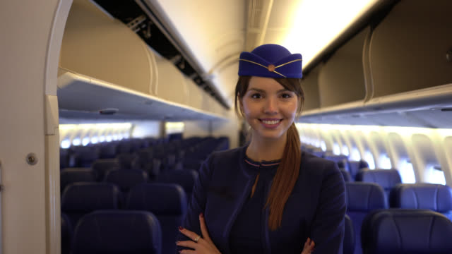 beautiful flight attendant walking down the airplane's aisle smiling at camera very happy - crew stock videos & royalty-free footage