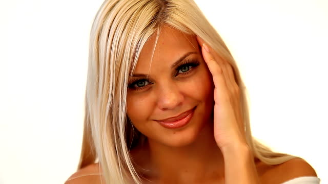 Beautiful flirting blonde woman touches her face