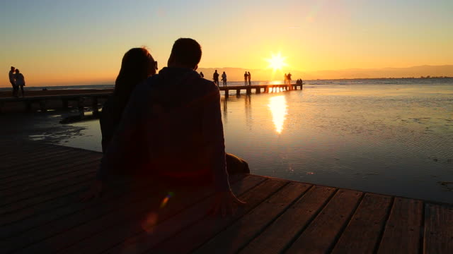 vidéos et rushes de beautiful footage of a couple in love sitting on pier contemplating the views during the sunset over the ebro delta landscape with the mediterranean sea during a travel in the catalonia region. - embrasser sur la bouche