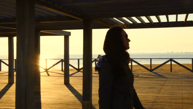 Beautiful footage of a woman walking on pier contemplating the views during the sunset over the Ebro Delta landscape with the Mediterranean Sea during a travel in the Catalonia region.