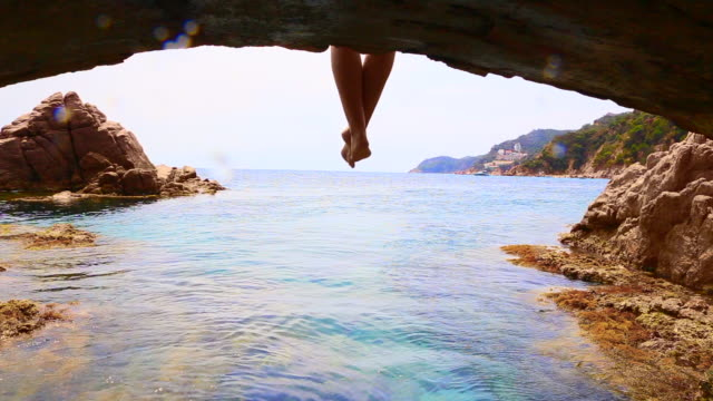 beautiful footage recording the legs of woman balancing from nice point of view while sitting and contemplating the costa brava mediterranean sea from arch over the sea with nice view. - legs crossed at ankle stock videos and b-roll footage