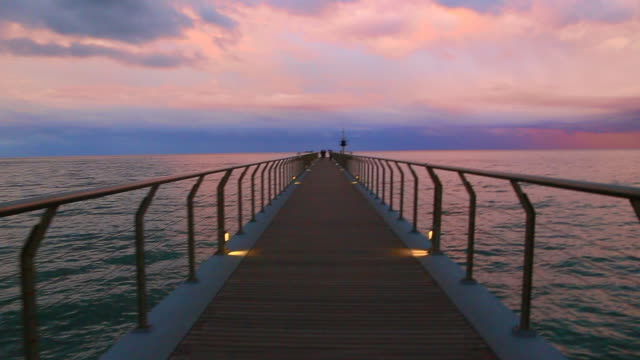 Beautiful footage with moving forward action walking from personal perspective in a stunning pier over the Mediterranean sea with vanishing point and infinity landscape during burning sky sunset in a unique and minimal place.