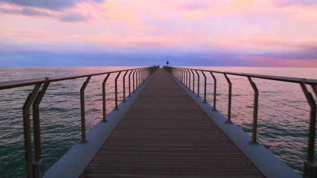 vídeos de stock e filmes b-roll de beautiful footage with moving forward action walking from personal perspective in a stunning pier over the mediterranean sea with vanishing point and infinity landscape during burning sky sunset in a unique and minimal place. - cais estrutura feita pelo homem