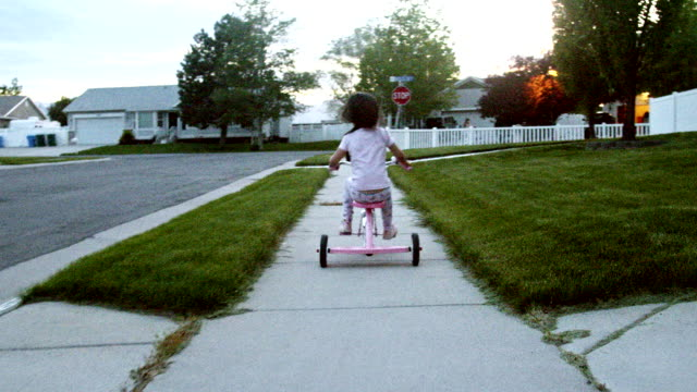 a beautiful four year old girl rides her tricycle along a sidewalk in a nice american middle class neighborhood in the summer time - tricycle stock videos & royalty-free footage
