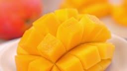 Beautiful fresh chopped mango, showing on a rotating white plate.