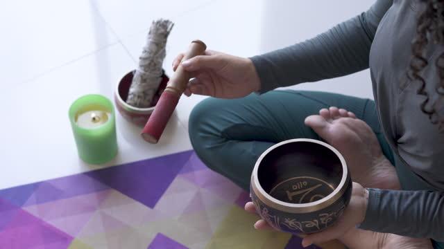 vídeos y material grabado en eventos de stock de hermosa mujer encrespada toca su instrumento para generar sonidos relajantes mientras hace su rutina de yoga en su estera de yoga - 30 39 years