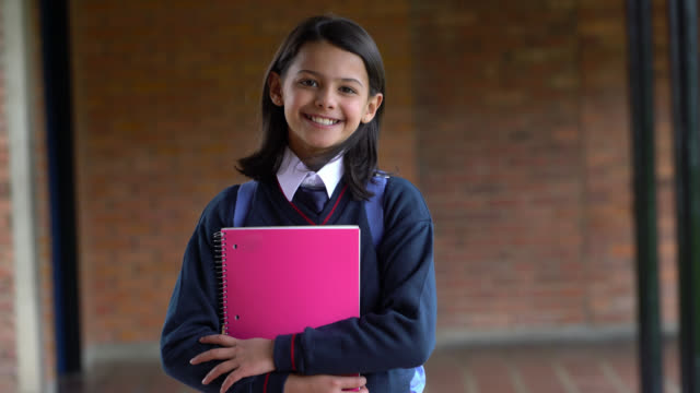 beautiful girl at her school grounds holding notebook and smiling at camera - school uniform stock videos & royalty-free footage