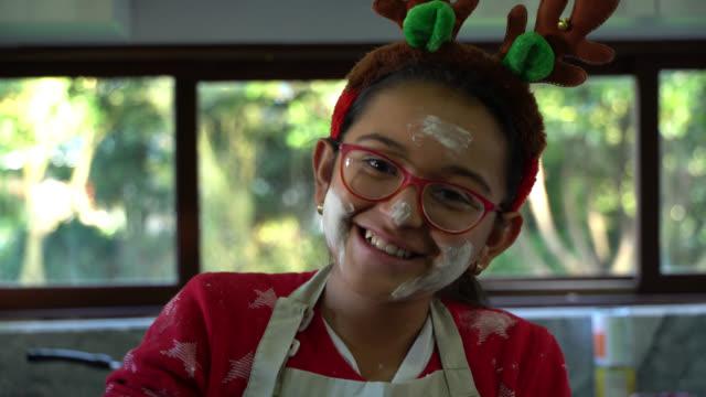 schöne mädchen backen etwas gegenüber kamera lächelnd mit ihrem gesicht voller mehl lachen datorund und tragen weihnachten reder hörner - keks stock-videos und b-roll-filmmaterial
