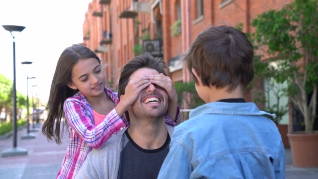 beautiful girl covering her father's eyes and little boy handing him a gift for father's day - fathers day stock videos & royalty-free footage