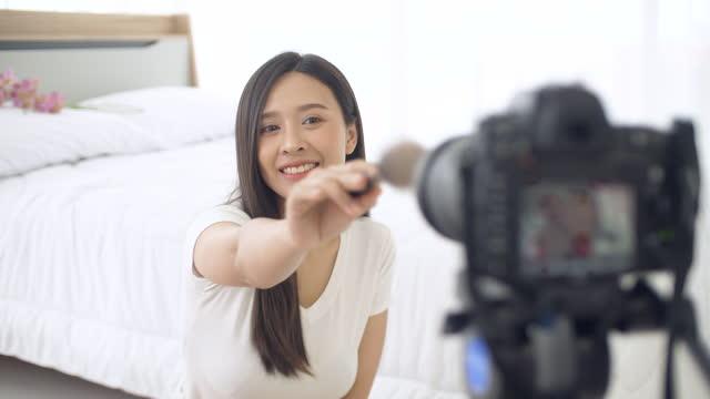 vidéos et rushes de belle fille créant la vidéo de tutoriel en ligne, cours en ligne - pinceau à blush