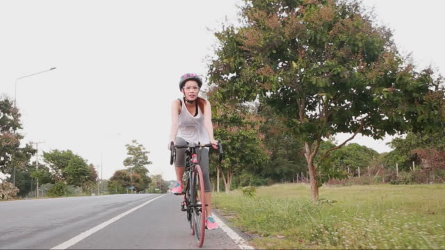 beautiful girl cycling in park - freestyle swimming stock videos and b-roll footage
