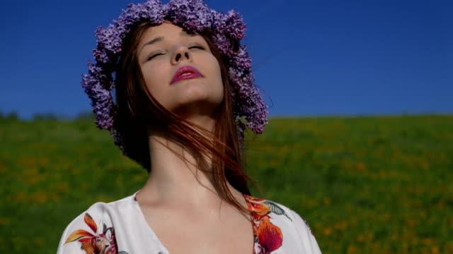 stockvideo's en b-roll-footage met een mooi meisje gekleed in een floral jurk is wandelen in het veld. - guirlande