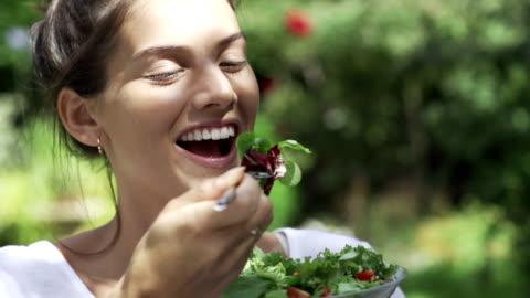 schönes mädchen essen salat in der sonne fo - gesunder lebensstil stock-videos und b-roll-filmmaterial