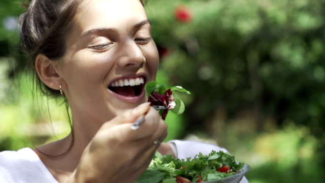 bella ragazza mangiare insalata al sole fo - piacere video stock e b–roll