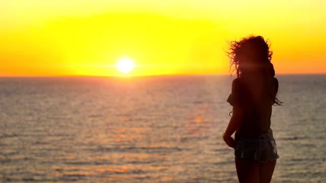 Beautiful girl enjoying amazing seascape during Sunset